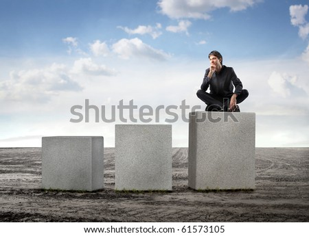 Businessman sitting on the highest of three cubes - stock photo