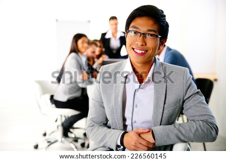 Businessman sitting on the office chair in front of business meeting - stock photo