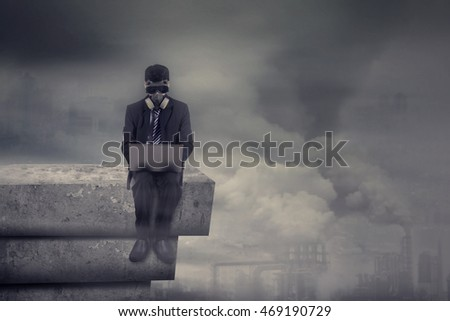 Businessman sitting on the rooftop while wearing mask and working with laptop computer