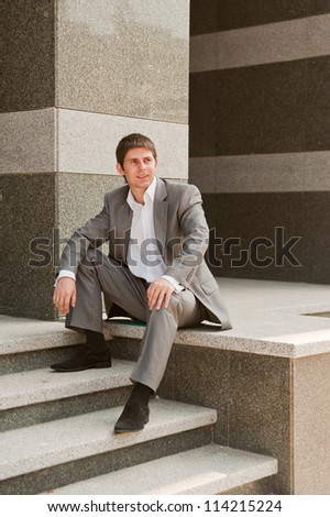 Businessman sitting on the steps the vertical frame