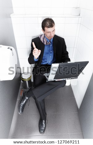 businessman sitting on the toilet having an idea - stock photo