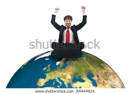Businessman sitting on the world while using his laptop - stock photo