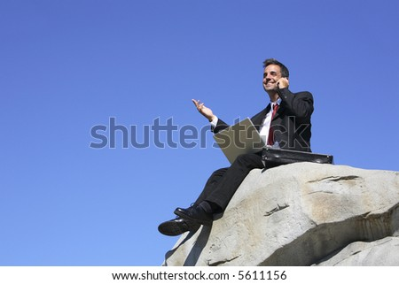 Businessman sitting on top of rock with laptop computer and cell phone - stock photo