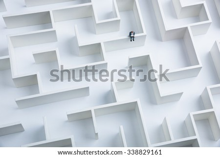 Businessman sitting on top of the labyrinth wall - stock photo