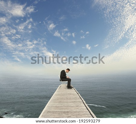 businessman sitting on wooden pier with laptop