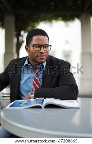 Businessman sitting outdoors reading Magazine - stock photo