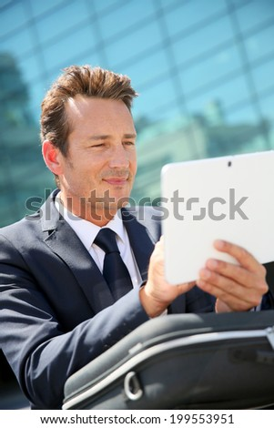 Businessman sitting outside office and using tablet - stock photo