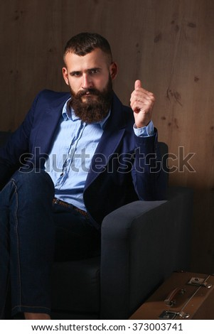 Businessman sitting the sofa in office lobby, isolated on dark background