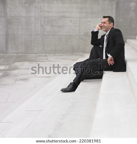 Businessman sitting while talking on cell phone - stock photo
