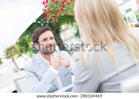 Businessman sitting with female colleague at sidewalk cafe - stock photo