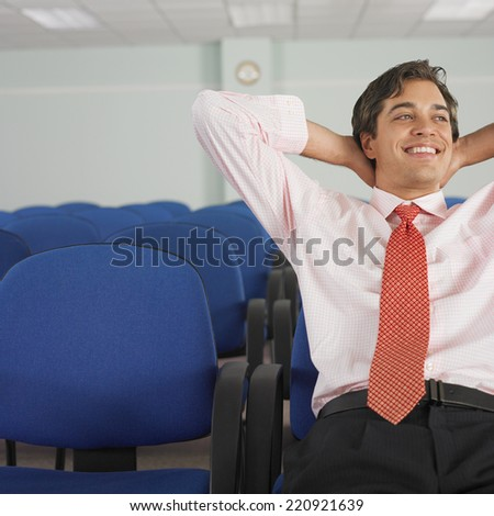 Businessman sitting with hands behind head - stock photo