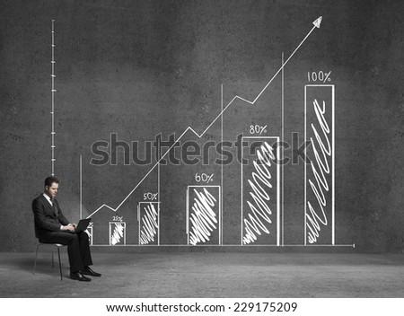 businessman sitting with laptop and drawing chart on wall - stock photo