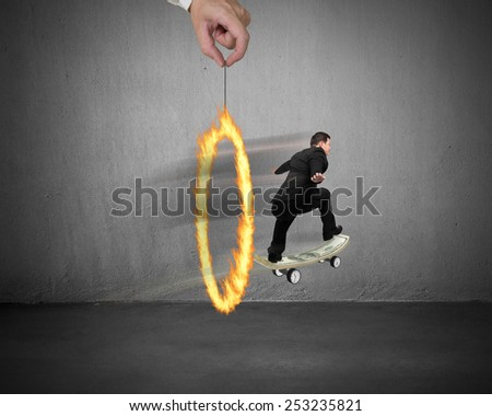 Businessman skating on money skateboard through fire circle with concrete room background - stock photo