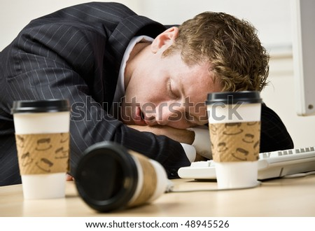 Businessman sleeping at desk - stock photo
