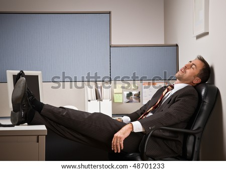 Businessman sleeping at desk with feet up - stock photo