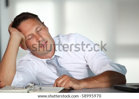 Businessman sleeping at his desk - stock photo
