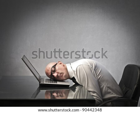 Businessman sleeping on a laptop - stock photo