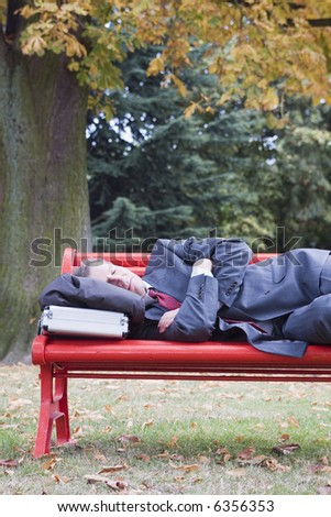 Businessman sleeping on a red parkbench in fall - stock photo
