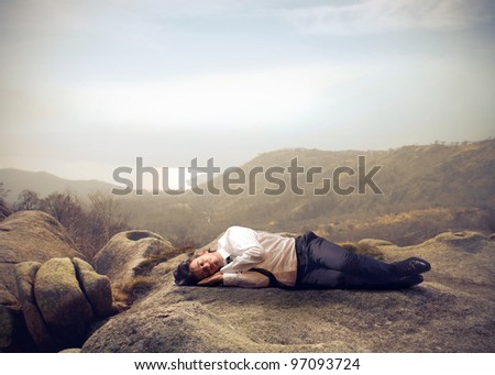 Businessman sleeping on a rock - stock photo