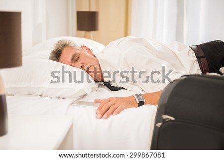 Businessman sleeping on bed after hard working day at the hotel room. Side view. - stock photo