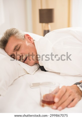 Businessman sleeping on bed after hard working day with glass of whiskey and his phone at the hotel room. Side view. - stock photo