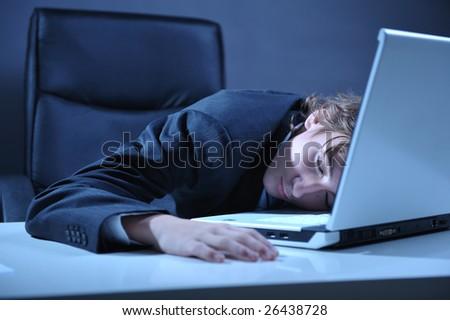 Businessman sleeping on desk near by computer laptop - stock photo