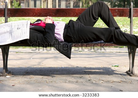 Businessman sleeping on the bench with newspapers on his head