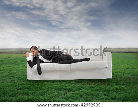 businessman sleeping on the sofa in a grass field - stock photo