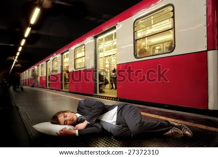 businessman sleeping on the subway floor - stock photo