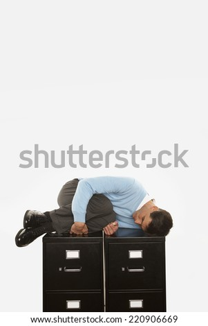 Businessman sleeping on top of filing cabinet - stock photo