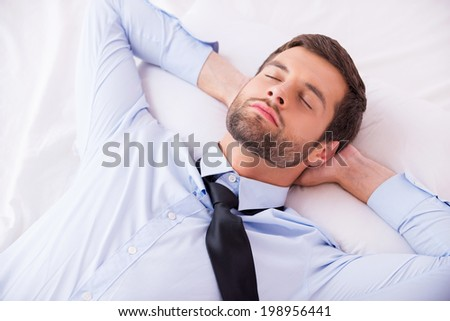 Businessman sleeping. Top view of handsome young man in shirt and tie holding hands behind head while sleeping in bed  - stock photo