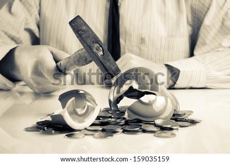 Businessman smashing piggy bank with hammer - stock photo