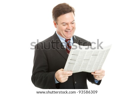 Businessman smiles as he reads his morning newspaper.  Isolated on white.