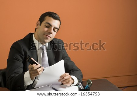 Businessman smiles as he staples papers while seated at his desk. Horizontally framed photo. - stock photo