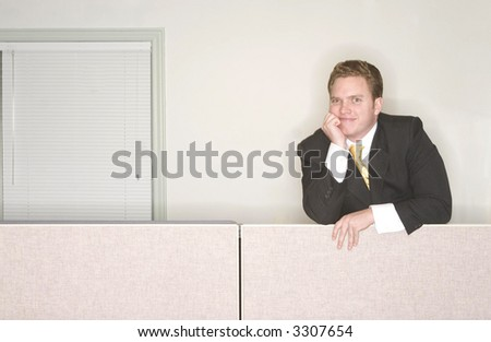Businessman smiles with his hand on his chin standing above his office cubicle