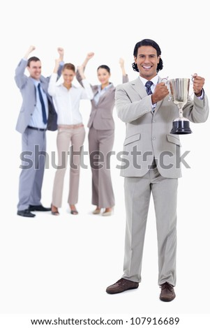 Businessman smiling and holding a cup with people cheering behind him against white background - stock photo