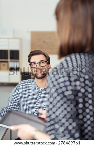 Businessman smiling as he listens to a female colleague as he sits at his desk in the office, view over her shoulder - stock photo