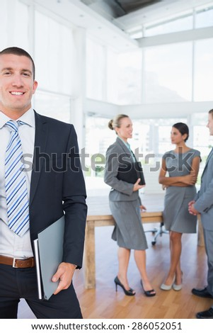 Businessman smiling at camera with colleagues behind him in the office