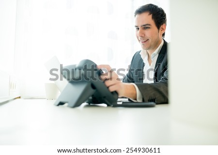 Businessman smiling in satisfaction after taking a phone call as he replaces the receiver on the hook, view through an interior partition in the office. - stock photo