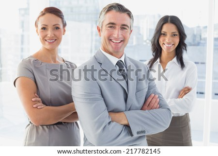 Businessman smiling with folded arms at work - stock photo