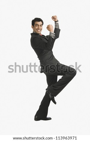 Businessman smiling with his arms raised - stock photo