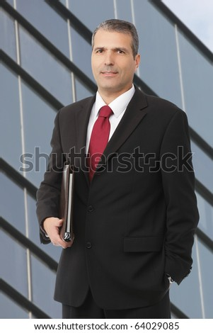 businessman smilling with notebook with colourfoul building background