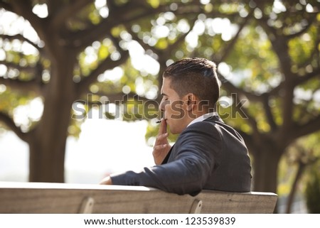 Businessman smoking a cigar to relax - stock photo