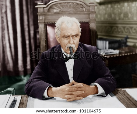 Businessman smoking cigar at desk - stock photo