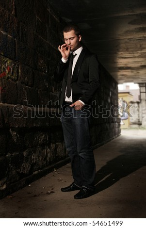 businessman smoking in tunnel - stock photo
