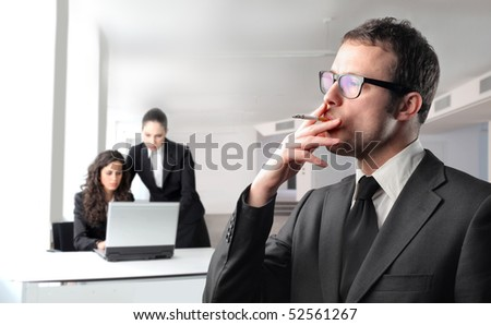 Businessman smoking with two businesswomen on the background - stock photo