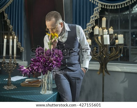 Businessman sniffing a bouquet of flowers in vase on the table