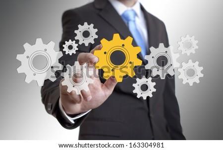 Businessman solution cogwheel concept - stock photo