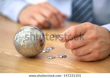Businessman solving globe puzzle concept for business solutions and strategy - stock photo