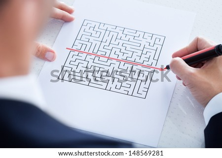 Businessman Solving Maze Puzzle With Red Pen